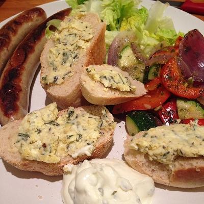 Gegrillte Bratwurst dazu Antipasti, grüner Salat, Zaziki, Baguette und Knoblauch-Rosmarinbutter