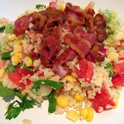 Couscous-Salat garniert mit krossen Speckstreifen